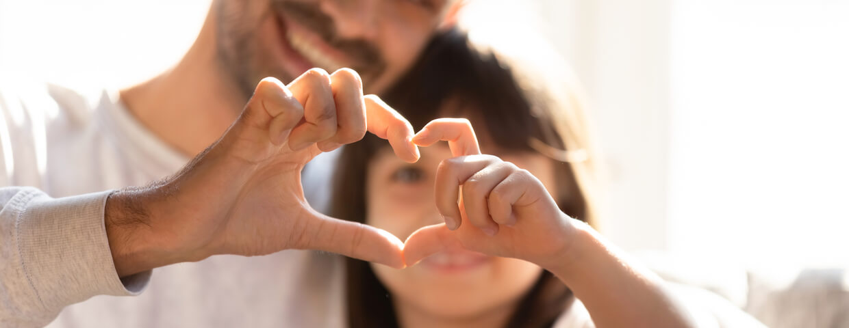 father and daughter, blurred image holding fingers together in a heart shape, teaching your children concept