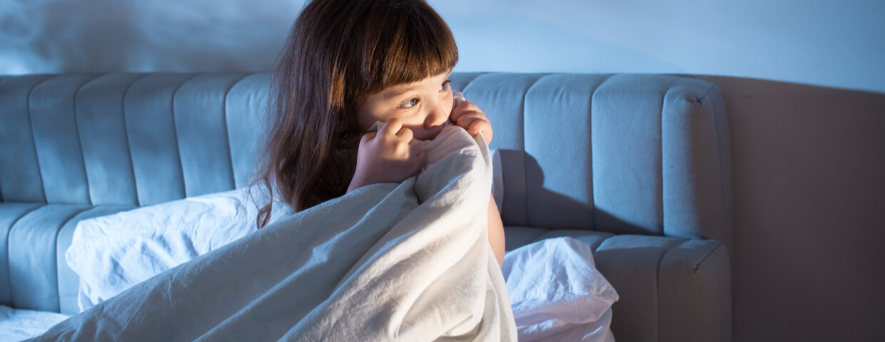 scared and awake little girl in bed pulling blanket up to her face, concept of sleep disorders for children, night terrors of the child, fear of the dark