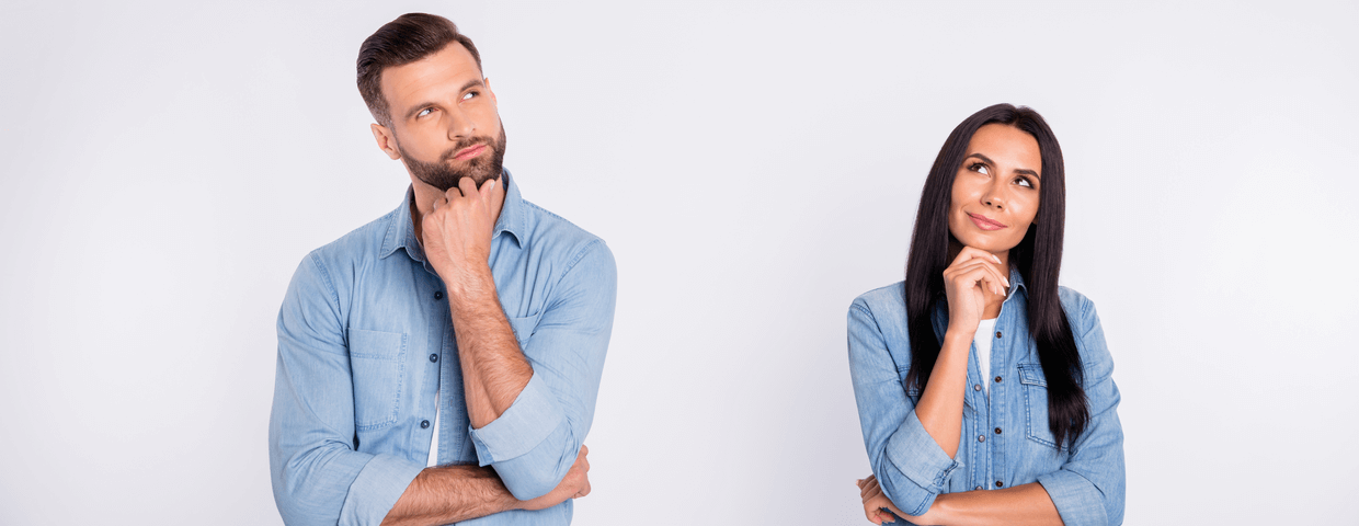 Man and woman standing side-by-side looking curious with one hand on their chins