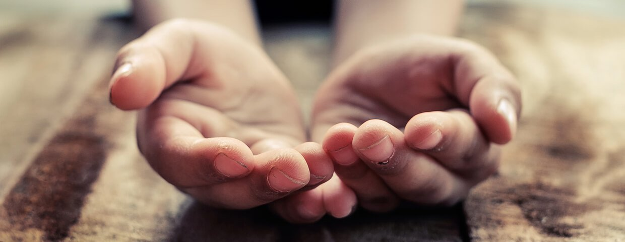 Close up of a child's hands open asking for help atop a wooden table