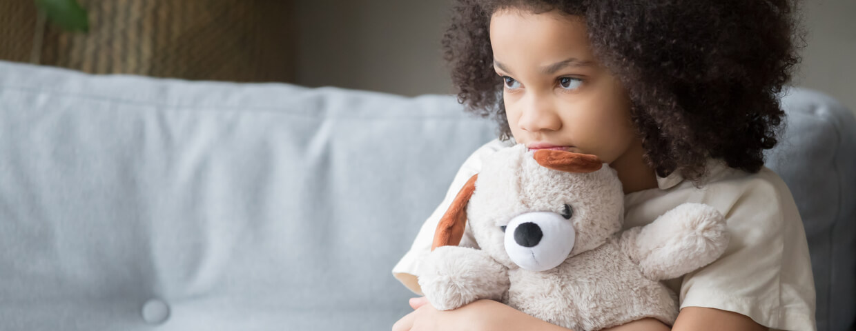 upset little girl holding teddy bear looking away, sad child in need, charity or nonprofit kids in need concept