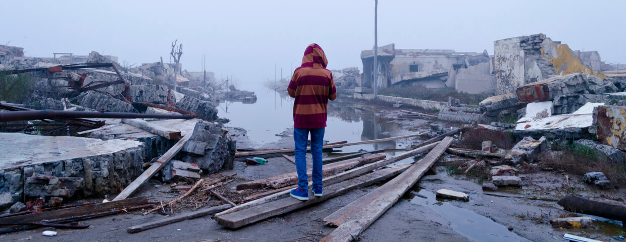 boy watching damage from a flood or natural disaster