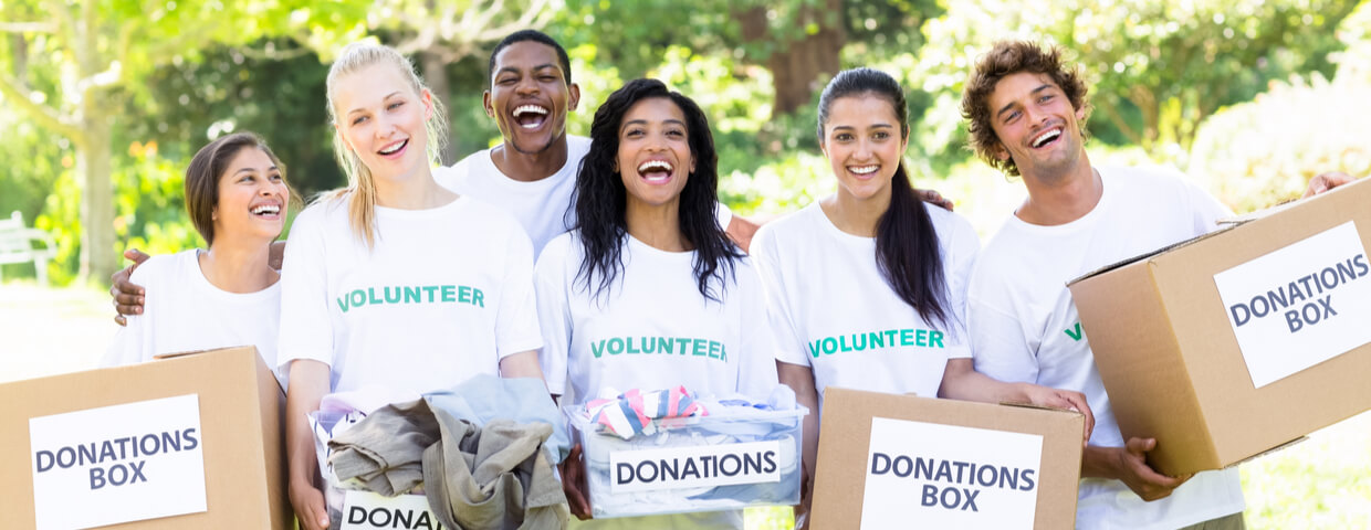 Group portrait of cheerful volunteers carrying donation boxes in park